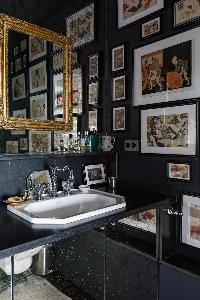 stylishly designed bath fullof framed artworks, and gilded mirror in a Paris luxury apartment