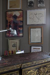 antique study desk, lamp, and framed artworks in a Paris luxury apartment