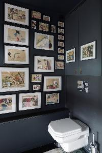 toilet in elephant grey hue with framed artworks in a Paris luxury apartment