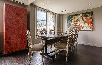 elegant dining area with wooden table for 6, oil painting, bright window with view of the city skyli