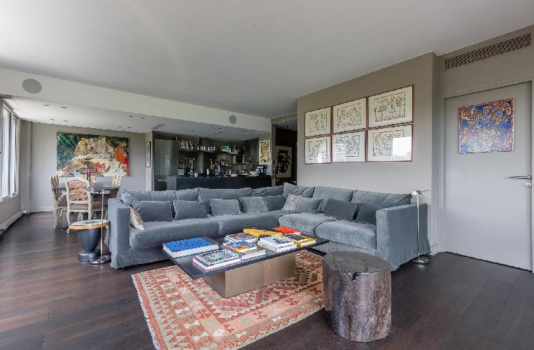 cozy living area with a collection of films and artworks, L-shaped grey sofa in a Paris luxury apart