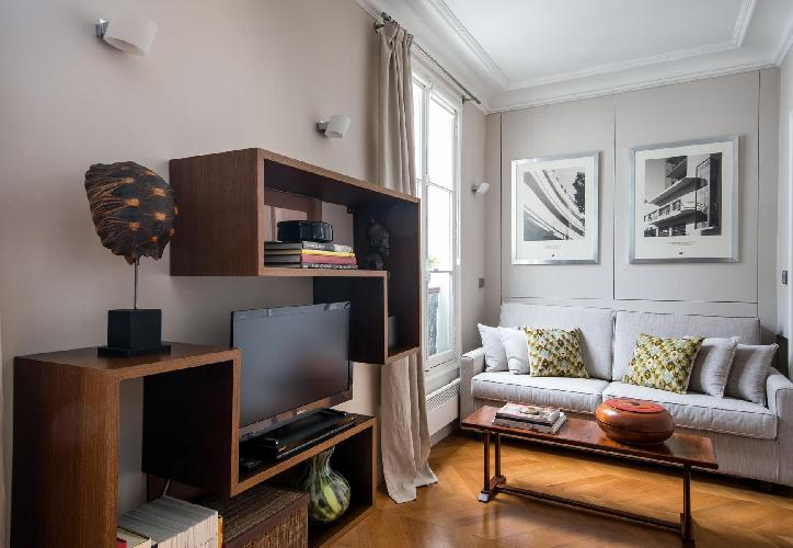 cream sofa with honeyed wood furniture, television, and black-and-white framed photographs in Paris