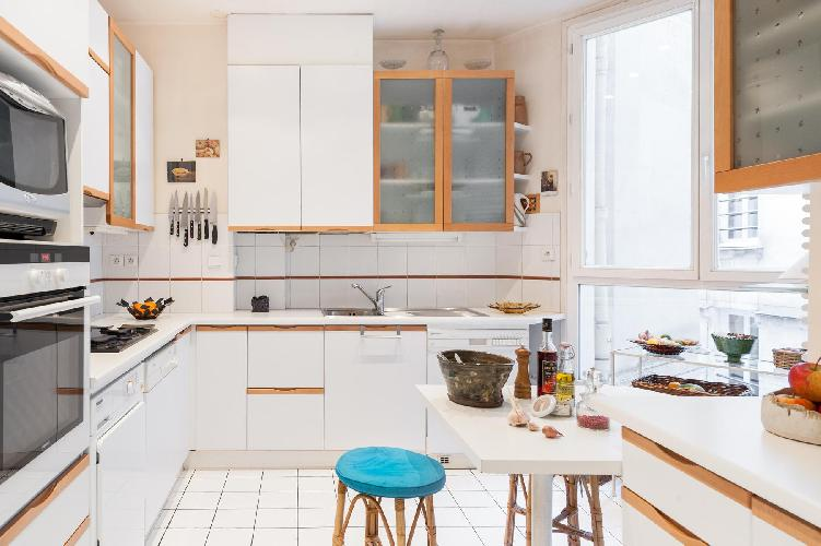 white and wood well-equipped kitchen with breakfast table and stool in a Paris luxury apartment