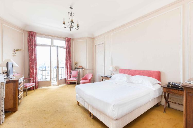 pretty bedroom in pink and white with Juliet balcony in Paris luxury apartment