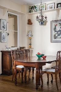 stylish chandelier beneath antique dining table surrounded by mahogany chairs in Paris luxury apartm