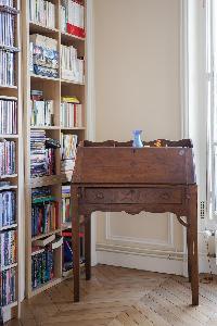 dark wood furniture and full bookcase in Paris luxury apartment