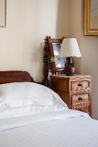 elegant master bedroom in neutral tones with dark wood furniture in Paris luxury apartment