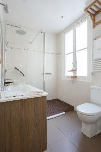 sleek bathroom in neutral tones in Paris luxury apartment