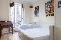 independent second bedroom with a double bed, dark wood furniture, and Juliet balcony in Paris luxur