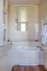 bath with sink and towel rack in a 2-bedroom Paris luxury apartment
