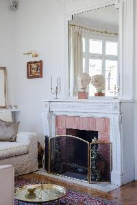 fireplace and elaborate mirror on top in a 2-bedroom Paris luxury apartment