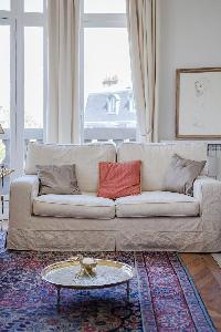 another sitting area cosy cream sofa in a 2-bedroom Paris luxury apartment
