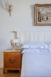 daintily decorated double bedroom with lovely armchair in a 2-bedroom Paris luxury apartment