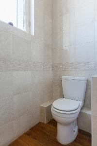 toilet with cream wall and wooden floor in a 2-bedroom Paris luxury apartment