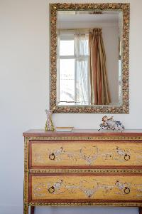 antique pieces, cabinet drawer, and elaborate mirror in a 2-bedroom Paris luxury apartment