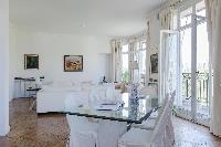 cream sofas, glass dining table, tall windows and cream drape curtains with spectacular view of the