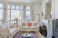 another sitting area with ornamental fireplace, and cosy cream sofas in a 2-bedroom Paris luxury apa