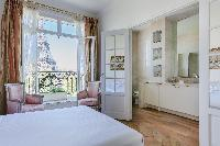 serene master bedroom with gilded furnishings, marble-tiled ensuite and a silk-curtained window over