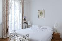 daintily decorated double bedroom with an ensuite shower room in a 2-bedroom Paris luxury apartment