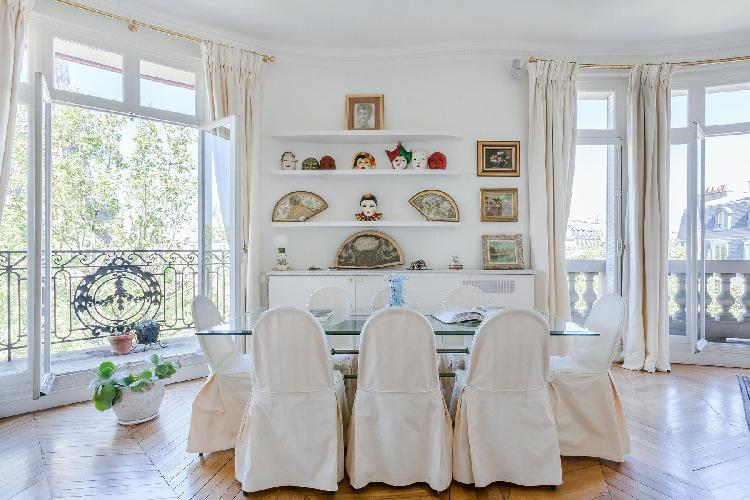 glass dining table for 8 with shelves lined with Venetian masks in a 2-bedroom Paris luxury apartmen