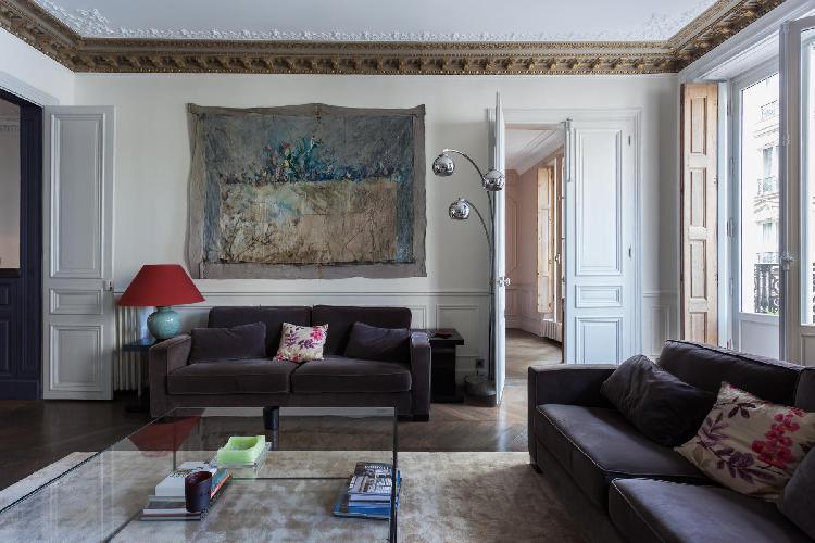 elegant living room with dark grey sofa, glass coffee table, Juliet balcony, and big framed artwork