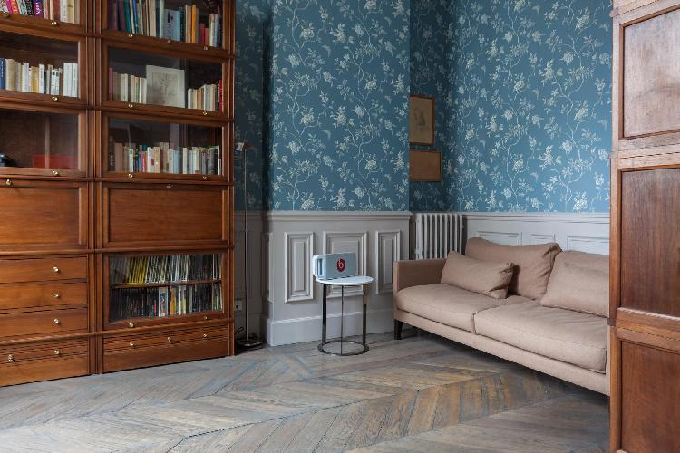 second sitting room with a low-slung sofa, library of books and patterned wallpaper in Paris luxury