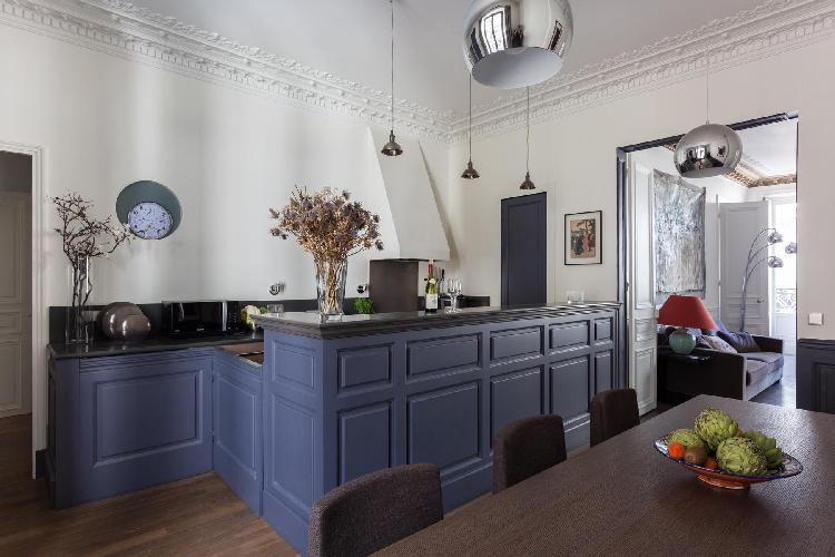 well-equipped kitchen with a long table, and cupboards painted royal blue in Paris luxury apartment