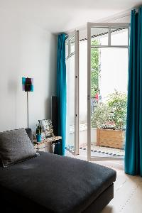 charcoal-colored sofa and teal draped window with access to the terrace in Paris luxury apartment