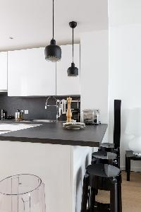 sleek white kitchen with black breakfast bar and stools in Paris luxury apartment