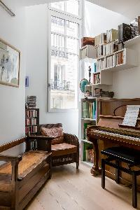 a piano, wooden bench and armchair in Paris luxury apartment