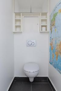 sleek white toilet with map on the wall in Paris luxury apartment