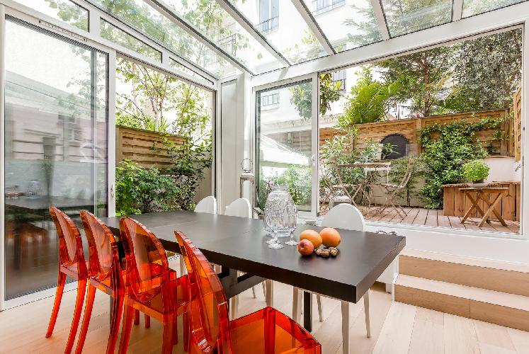 glass-roofed dining area and a second terrace with a little lawn in Paris luxury apartment