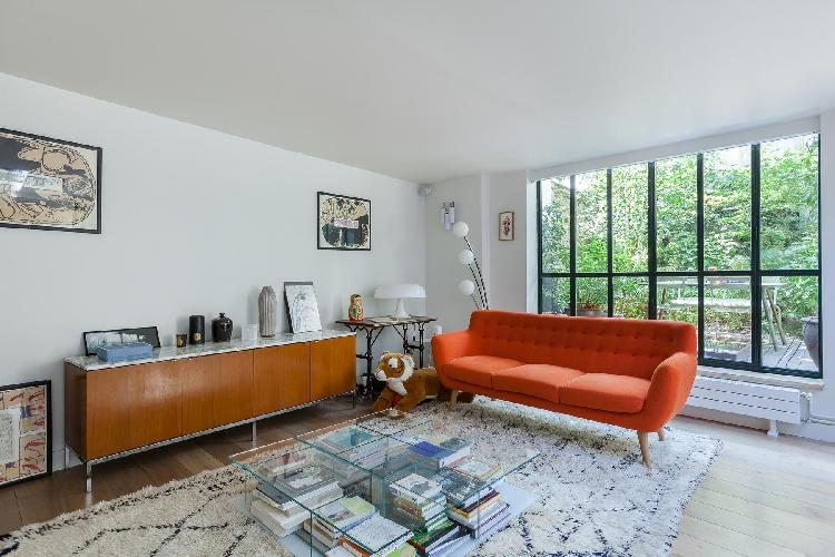 cozy living area furnished with tangerine sofa in Paris luxury apartment