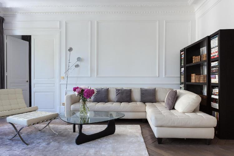 a modern living area with a dusky parquet floor, cream leather sofa and bookshelves in a 3-bedroom P