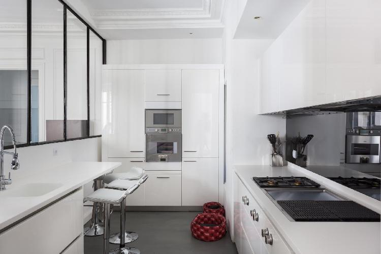 white well-equipped kitchen with glass wall  kitchen counter and stools in a Paris luxury apartment