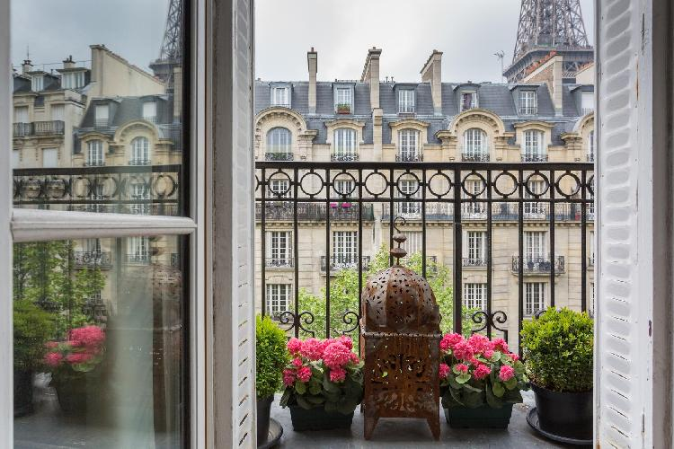 stunning view from the window withpotted flowery plants in a 2-bedroom Paris luxury apartment