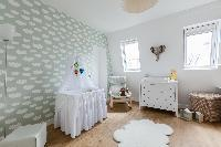 cozy second bedroom with a crib, double bed, and air-conditioning with white-painted walls and styli