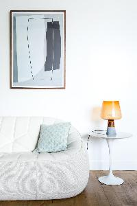 white sofa beside a yellow stylish lamp beneath framed abstract artwork in Paris luxury apartment