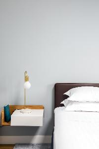 pale-painted wall with bed and white lamp in Paris luxury apartment