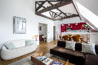 cozy living room with brown velvet and white sofas, TV, iPod dock, wooden dining table and chairs, a