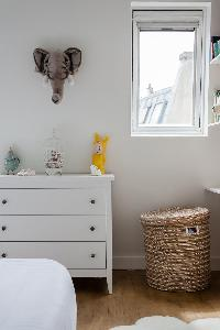 white cabinet drawer, toy basket, and elephant head wall design in Paris luxury apartment