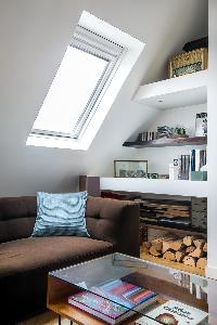 brown sofa, shelves, glass coffee table, and eaves wall in Paris luxury apartment
