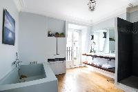spacious en suite bathroom with a basin, bath, shower, and Juliet balcony in Paris luxury apartment