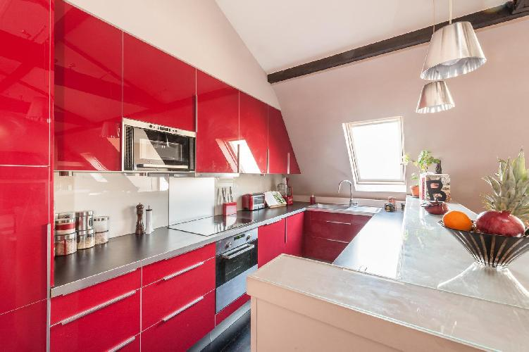 red well-equipped kitchen with a breakfast bar in Paris luxury apartment