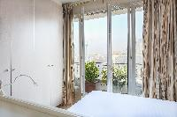 tall draped window opened up to the balcony overlooking Paris