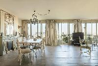 elegant dining table for 8 beneath a stylish chandelier, surrounded with cream draped windows in Par