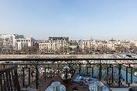 wooden coffee table and chairs in balcony with view of Paris