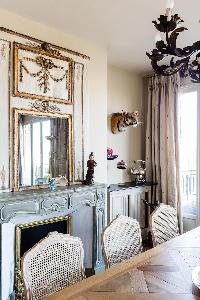 elegant dining table and chairs and ornamental fireplace in Paris luxury apartment