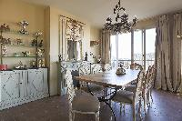elegant dining area with vases, silverware, and exotic statuettes in every corner in Paris luxury ap