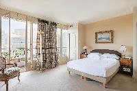 cozy master bedroom with queen-size bed, antique furnishings, and windows open onto the balcony in P